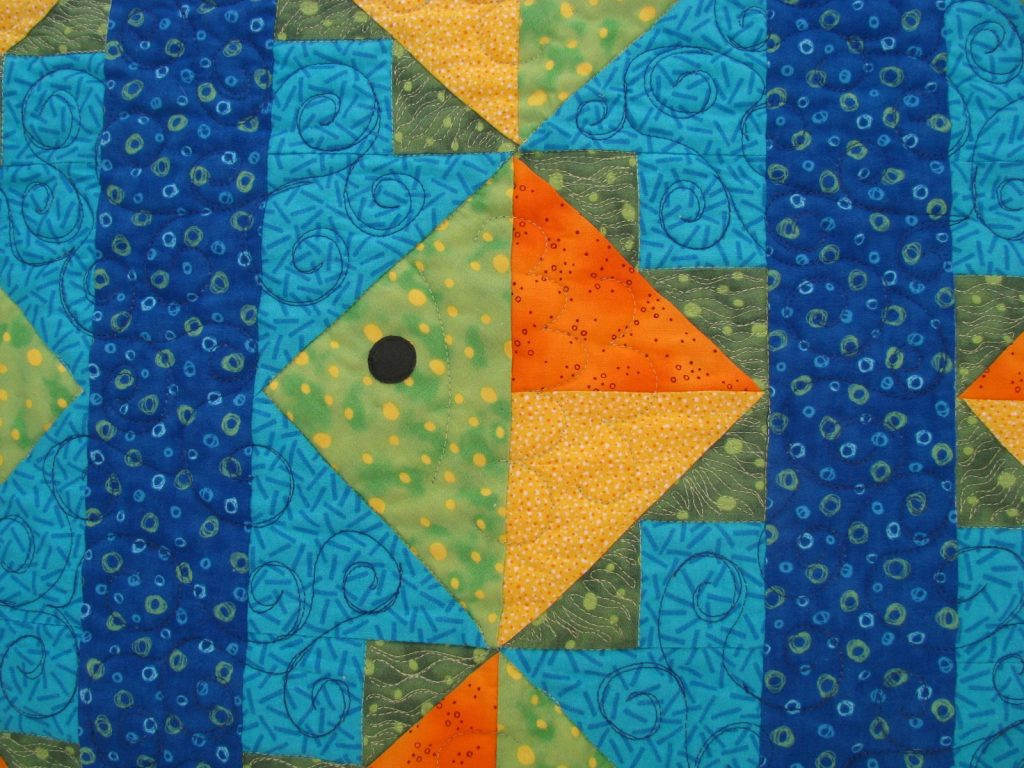 Flying Fish Quilt by Jean Ann Wright, Fish on dark background closeup