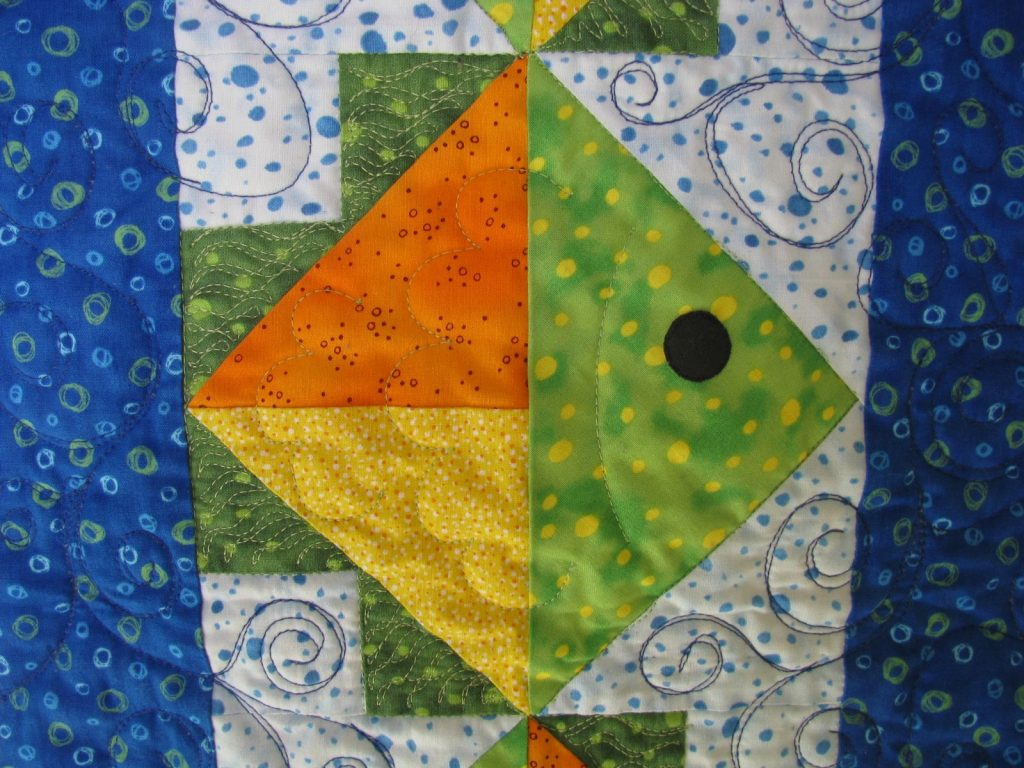 Flying Fish Quilt by Jean Ann Wright, Fish on light background closeup