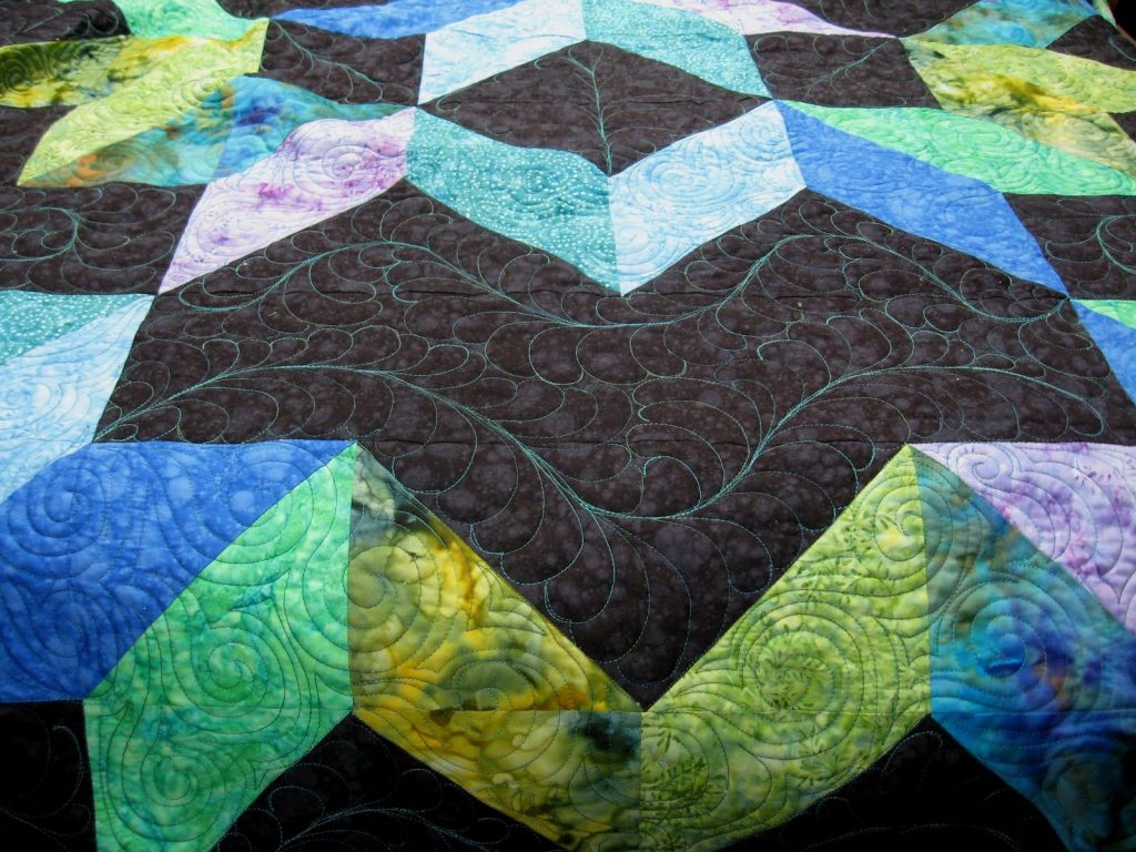 Cosmic Jewels (carpenter star), Feather quilting in the background